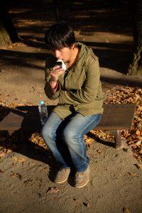 公園で寂しくおにぎりを食べる男性
